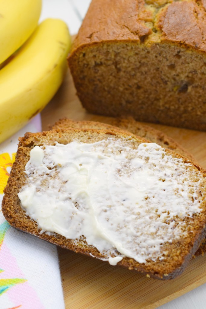 slice of buttered banana bread next to bunch of bananas and loaf on wood board