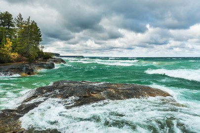 Lake Superior churns around the shoreline at Pictured Rocks under dramatic skies