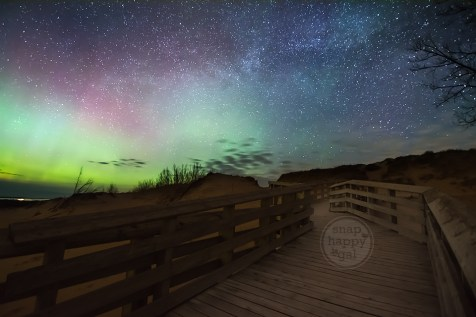 A Sleeping Bear Dunes boardwalk meanders under a starry night sky alive with dancing Northern Lights