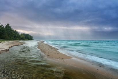 Light rays shine through moody clouds over Lake Michigan at Shalda Creek