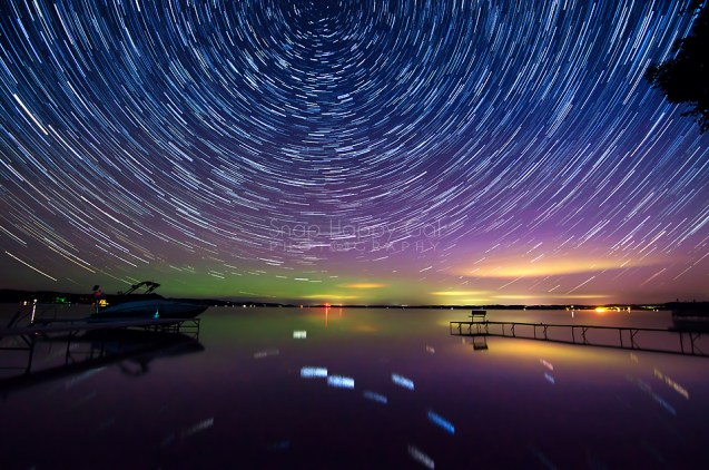 Photo: Stars circle above an aurora filled night sky overlooking Alden, Michigan