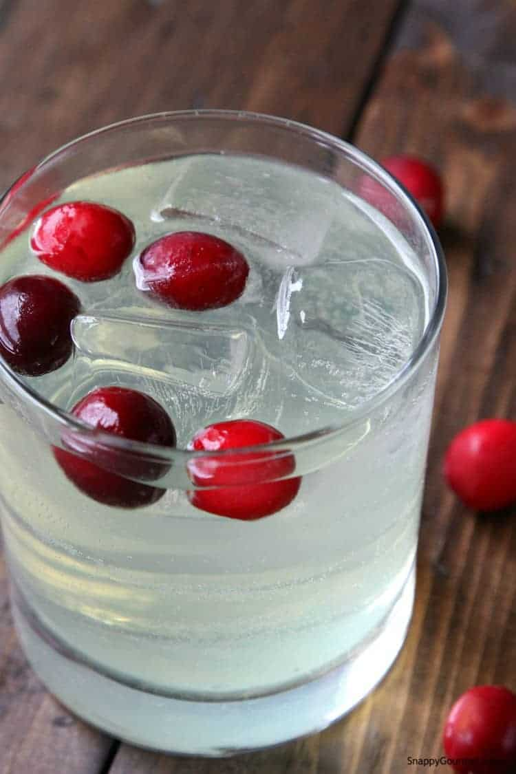limoncello spritzer in glass with ice and frozen cranberries