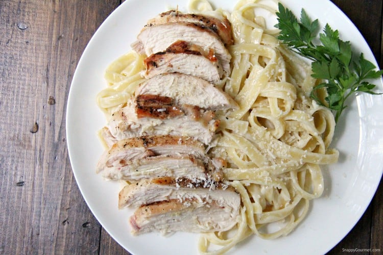 fettuccine alfredo with from scratch alfredo sauce and grilled chicken slices on plate