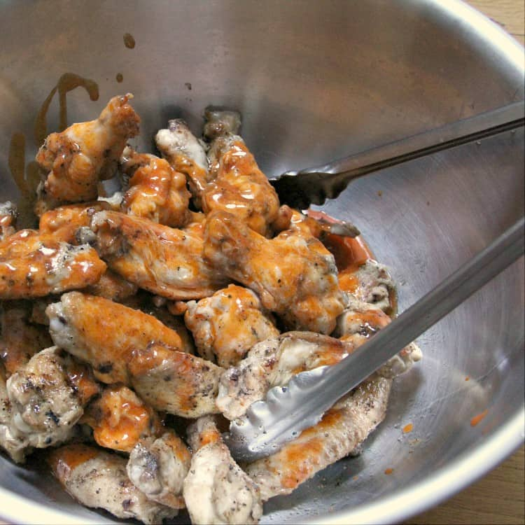 grilled wings in bowl being tossed with buffalo sauce