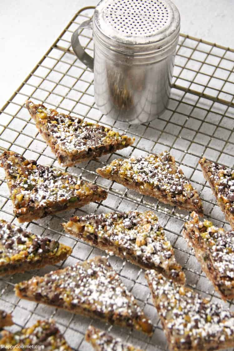 Cannoli Magic Bars on wire rack with powdered sugar