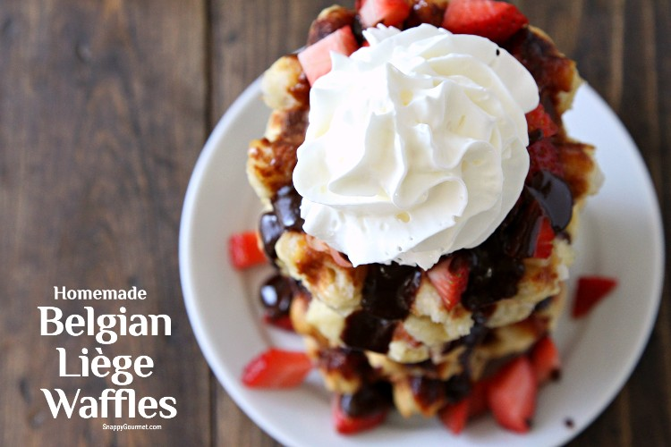 stack of authentic belgian waffles on plate with strawberries, chocolate sauce, and whipped cream