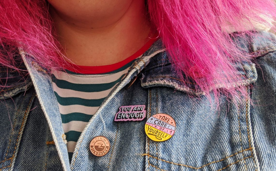 pmdd close up of denim jacket with enamel pins. pink haired person.