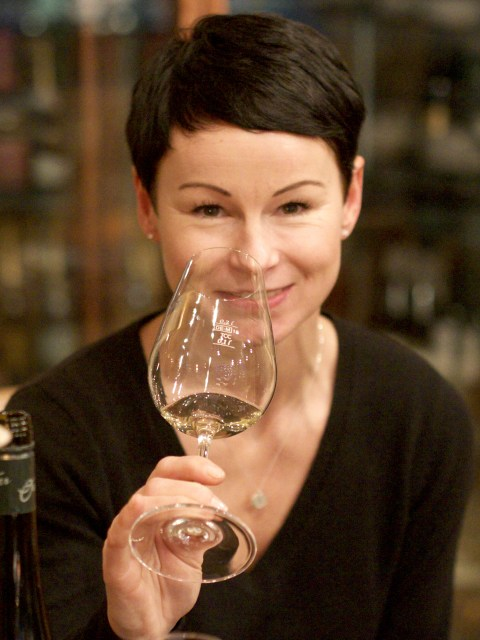 Anja Schröder, owner of Planet Wein in Berlin, holding a wine glass and smiling.