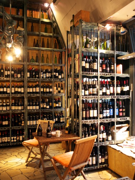 Table with chairs and wine bottles in front of many shelves of wines at Planet Wein in Berlin.