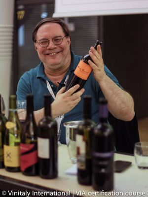 Ian D'Agata holding a wine bottle while teaching at the Vinitaly International Academy