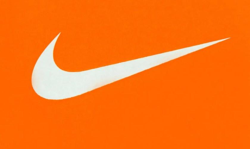 White Nike Logo on Orange Background;Nike, Inc. is an