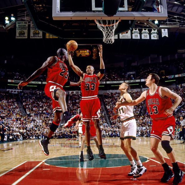 Scottie Pippen & Michael Jordan of the Bulls respectively wearing the Nike Air More Uptempo & the Jordan XI'Playoff' and Luc Longley of the Bulls, wearing Nike Air Max Uptempo, against Detlef Schrempf of the Sonics, wearing the Adidas EQT BB Image via Getty/Andrew D. Bernstein