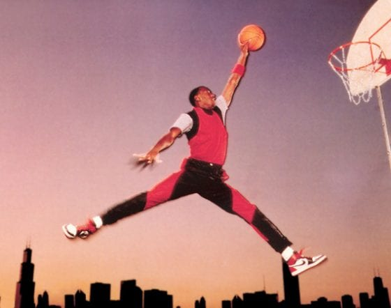 MJ in a Nike jumpsuit and Jordan 1s jumping above the Chicago skyline