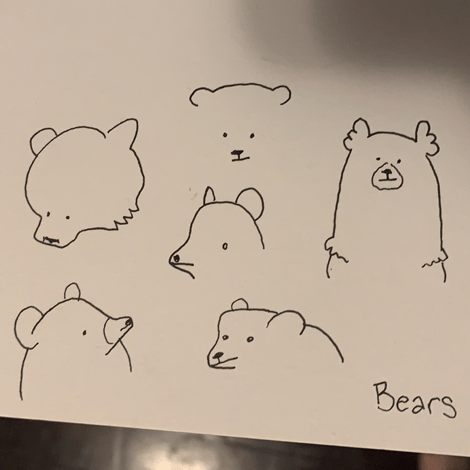 "A photograph of a sketchpad page showing six bear heads -- they are all a little different from each other, but all of them are very cute. In the corner is written the word ""bears."""