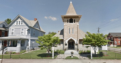 Google Street View image of a very cute little grey stone church on the corner of a block. It is next to the blue house that the article is about.