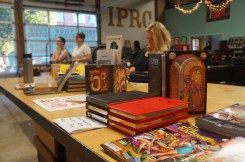 "Mark Russell's books and comics front-and-center while Jenny Forrester plays in the ""creativity corner"" (all photos by LS)"
