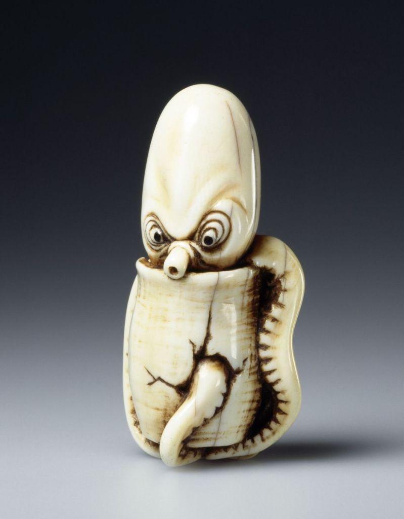 """Oktopus in einem Topf Krakenfleisch war lange Zeit ein Armeleuteessen. Hier schaut ein Krake (tako) aus einem Fangtopf hervor. Die Falten um seine Augen drücken sowohl seine Verärgerung über das """"Gefängnis"""" aus als auch die Anstrengung, sich aus der misslichen Lage zu befreien. Netsuke aus Elfenbein, Pupillen aus Horn, Japan, 2. Hälfte 19. Jh., Linden-Museum Stuttgart, Slg. Trumpf, Stiftung 1966, Foto: A. Dreyer, Inv.-Nr. OA 19.234 (TN 492)"""