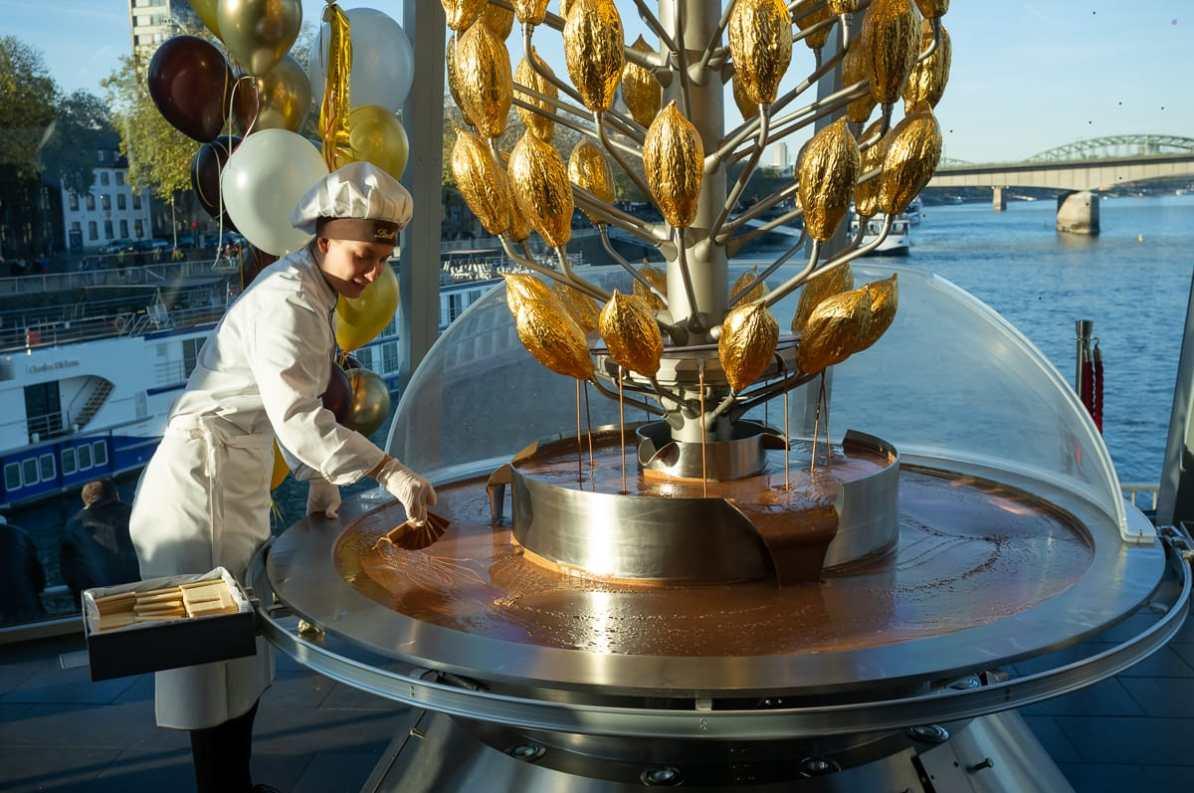 Lindt-Mitarbeiter bereiten die Waffeln mit Schokolade aus dem Brunnen für Besucher vor
