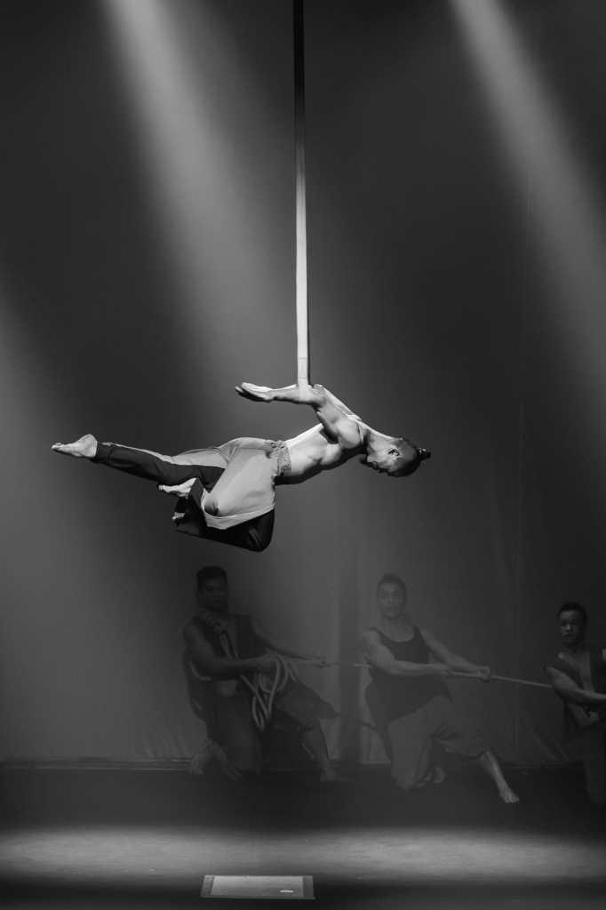 """Kraftvolle Akrobatik (Strapaten, Künstler hängt an den Unterarmen an Seilen in der Luft) und Absicherung durch die Kollegen bei """"Sông Trăng""""."""