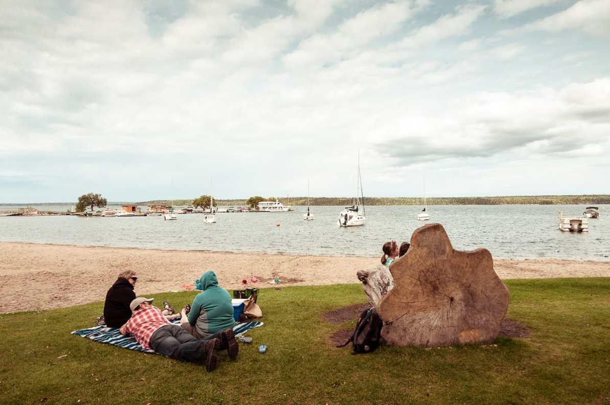 Am Ufer des Clear Lakes in Wasagaming sitzt eine Familie auf einer Picknickdecke.