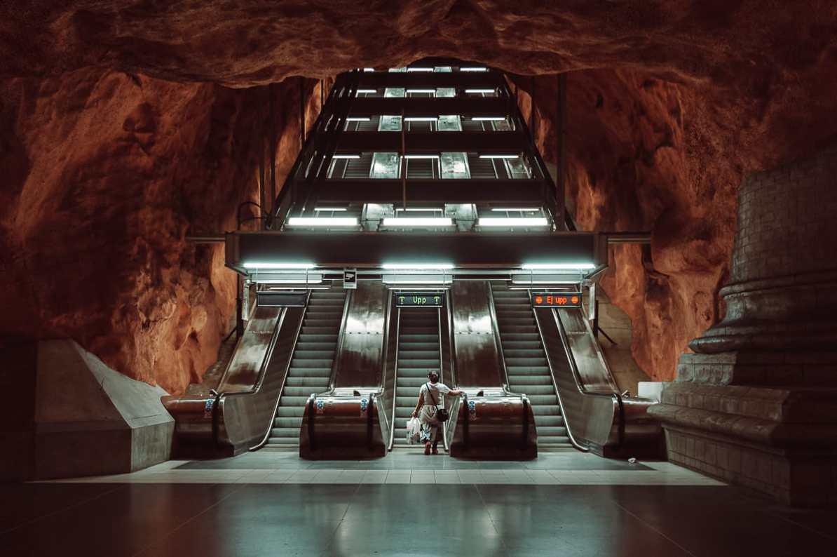 Tunnelbana-Haltestelle Rådhuset, Stockholm - 3 Rolltreppen mit einer Frau in der Mitte, griechische Säule rechts