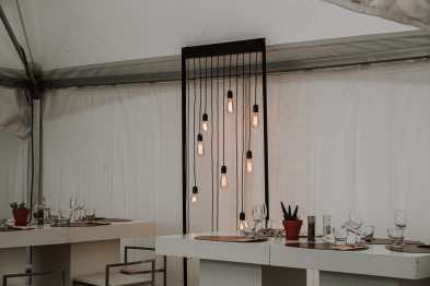 """Inneneinrichtung eines Zeltes beim """"Les Epicuriales"""" - Hängelampen in einem Rahmen im Hintergrund, gedeckter Tisch vorne"""