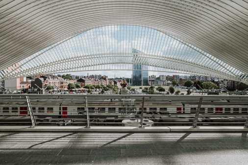 Bahnhof Liège-Guillemins mit Blick über die Gleise, mit dem Tour Paradis im Hintergrund, die Welle des Dachs ist sichbar.