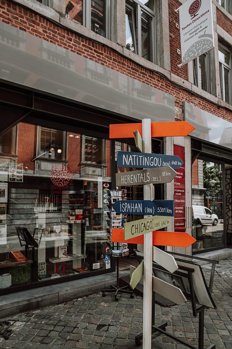 Wegweiser in verschiedene Richtungen mit verschiedenen Orten und Entfernungen vor dem Reisebuchladen Toutes Directions, Lüttich