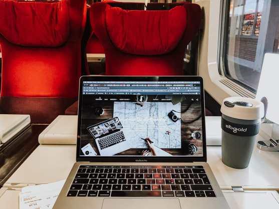 Arbeiten im Thalys - Laptop und Kaffeebecher auf dem Tisch, rote Sessel im Hintergrund