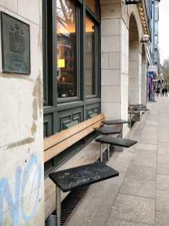 Außensitzplätze mit fest montierten Tischen und Bänken am Fenster von Otto's Burger Schanze.