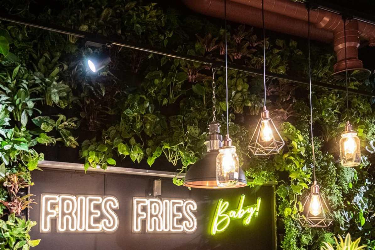 Fries Fries baby-Leuchtschrift im Erdgeschoss, umgeben von vielen Pflanzen, davor einige Lampen im Industriestil.
