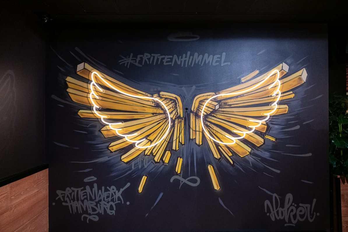 Instagramable Spot - Frittenhimmel-Graffito mit Engelsflügel aus Pommes