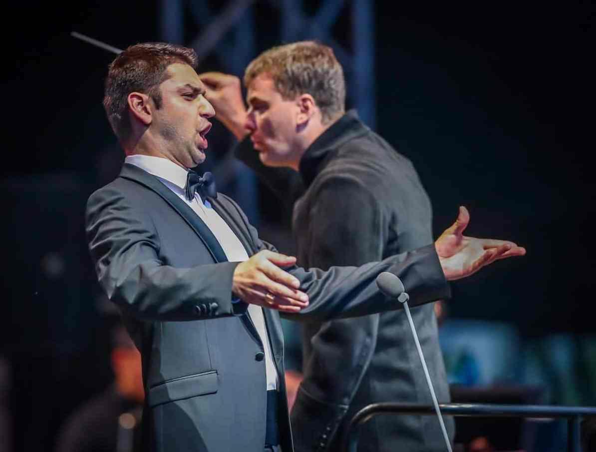 Denis Velev während des Singens, GMD der Dortmunder Philharmoniker Gabriel Feltz im Hintergrund, Foto: Jan Heinze/Stephan Schütze