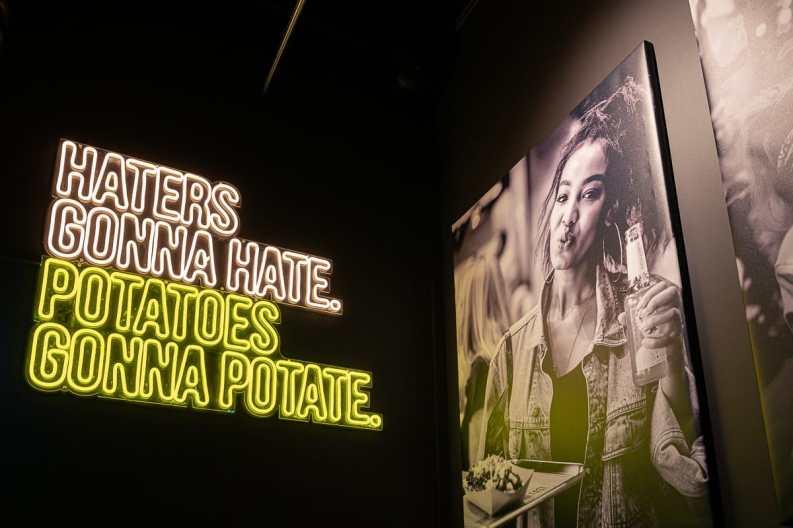 Haters gonna hate, potatoes gonna potate - Leuchtschrift in der hintersten Ecke.