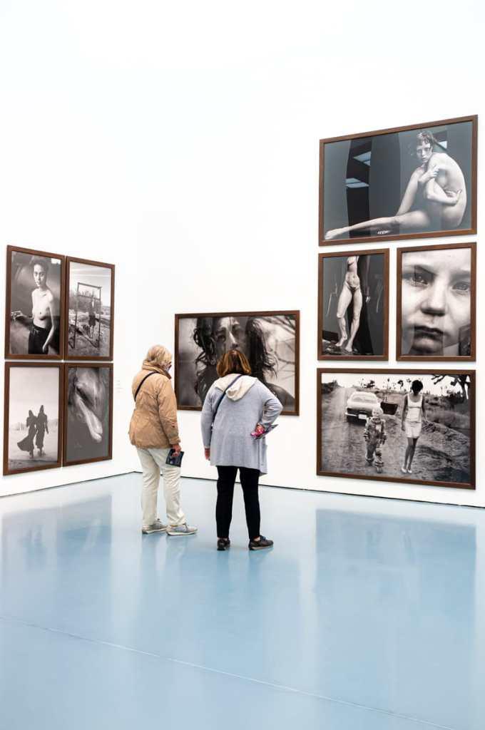 """Peter Lindberg, """"Untold Stories"""" - Teile der Ausstellung inkl. dem Foto des Delfins auf der linken Seite. Im Bild sind zwei Personen zu sehen, die sich andere Fotos daneben ansehen."""