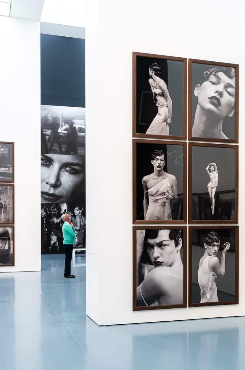 Blick auf die zweite Fototapete zwischen den Wänden hindurch, im Vordergrund eine Reihe von Fotos von Milla Jovovich.