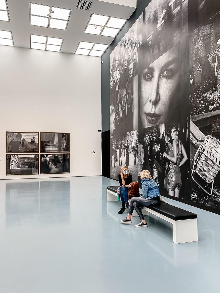 Zwei Frauen sitzen vor der zweiten Fototapete auf einer Bank, ins Gespräch vertieft.