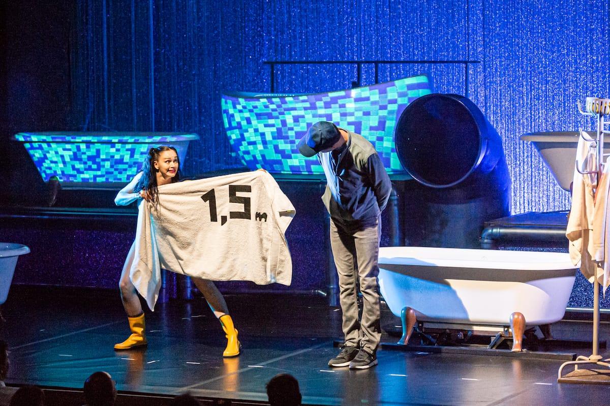 Coronaregeln werden humoristisch in eine Nummer eingebaut - Handtuch mit 1,5 m-Aufschrift.