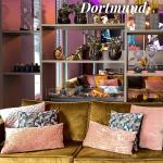 Pinterest-Grafik passend zum Artikel mit Bild aus dem Restaurant mit gemütlicher Couch mit vielen Kissen in der offenen Lobby, ein aufbereiteter Pin mit Text-Overlay.