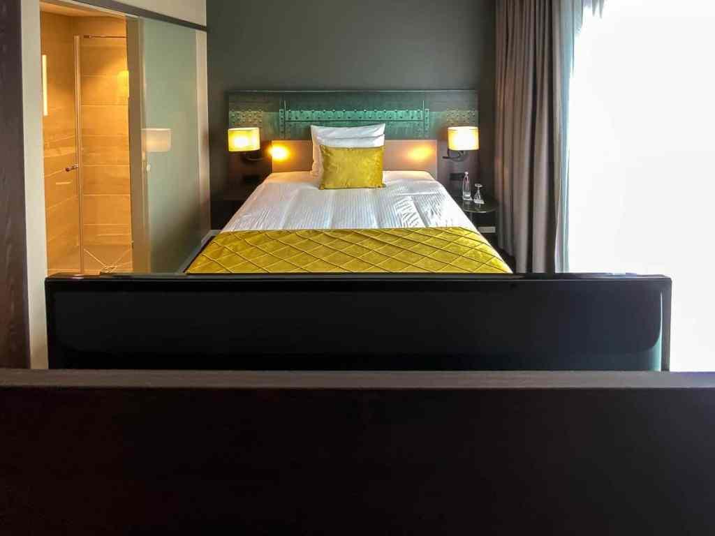 Blick über den drehbaren Flatscreen auf das Bett im Deluxe Zimmer.