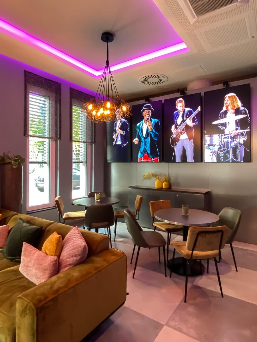 Band auf Bildschirmen in der Bar des Leonardo Dortmund Hotels