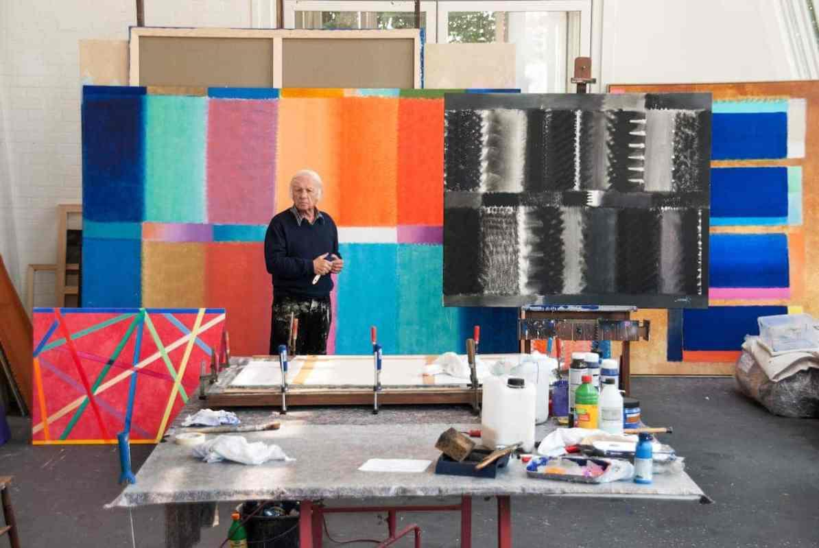 Heinz Mack in seinem Atelier in Deutschland, 2013 (Foto: Archiv Atelier Heinz Mack) - Arbeitsfläche /Tisch teilweise mit Malutensilien vollgestellt, dazu ein Bild eingespannt in Schraubklemmen auf dieser Arbeitsfläche, dahinter Heinz Mack mit farbverschmierter Hose vor mehreren großflächigen Gemälden (farbig und schwarz/weiß)