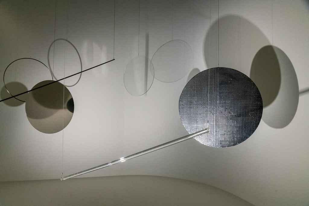 9-teilige Installation Rondo aus Kreis- und Stangenelementen, die Schatten werfen und Licht reflektieren mit dunklerem Schatten und Reflexion