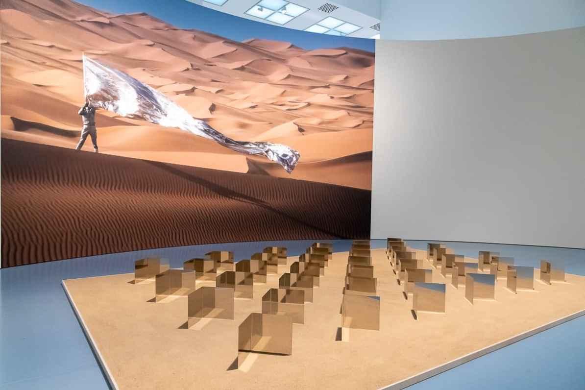 Sahara-Relief, 2011, Edelstahl, Sand, 91 Elemente, dahinter ein Foto von Heinz Mack mit Silberfahne im Grand Erg Oriental/Algerien (1976) von Thomas Höpker (Courtesy Archiv Atelier Heinz Mack, Heinz Mack/VG Bild-Kunst, Bonn, 2021)