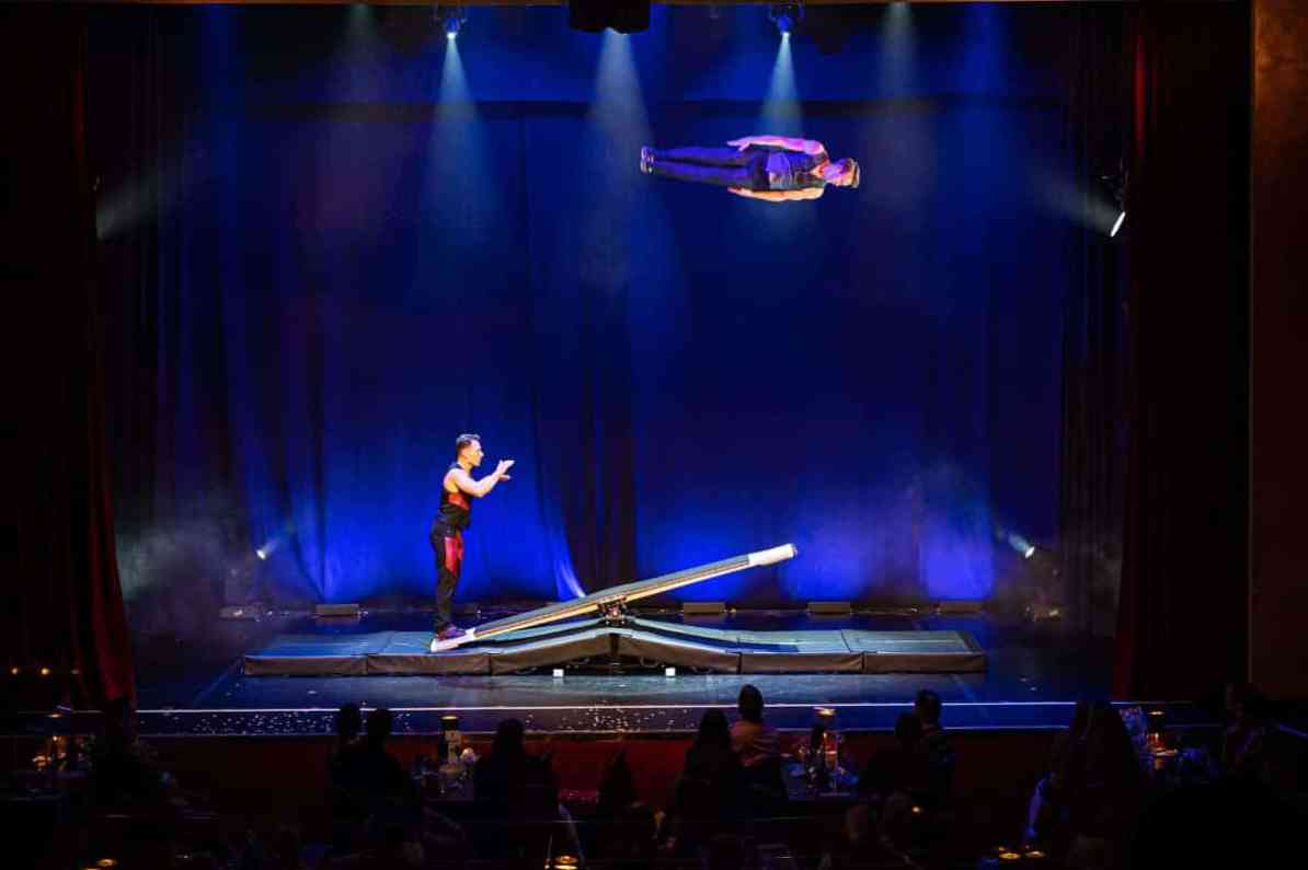 Duo Stepout während der Akrobatiknummer. Einer fliegt oben waagerecht in der Luft, der andere ist auf dem Brett links gelandet.