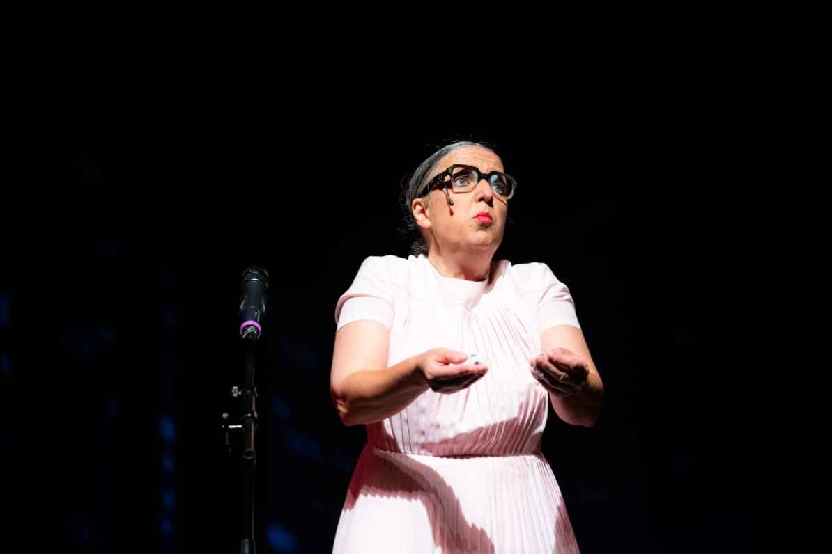 Komikerin Rosemie auf der Bühne des GOP in rosa Kleid sowie mit dicker Hornbrille.