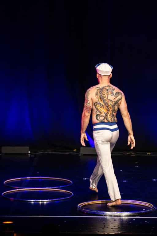 """""""Le Male"""" Tigris, der mit nacktem Oberkörper und mit dem Rücken zum Publikum steht und einen Schritt aus einem Stapel Hula Hoop Ringen macht. Auf dem Boden liegen weitere Hula Hoop Reifen. Auf seinem Rücken ist ein riesiges Tiger Tattoo zu sehen. Er ist barfuß, mit einer maritimen Hose bekleidet, dazu einen Matrosenhut."""