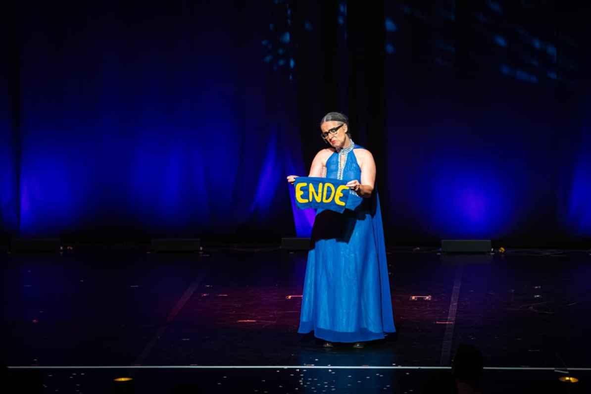 """Alles hat ein Ende, auch """"Wild Boys"""". Rosemie hält in einem langen blauen Abendkleid ein Stoff mit dem Wort """"Ende"""" hoch."""