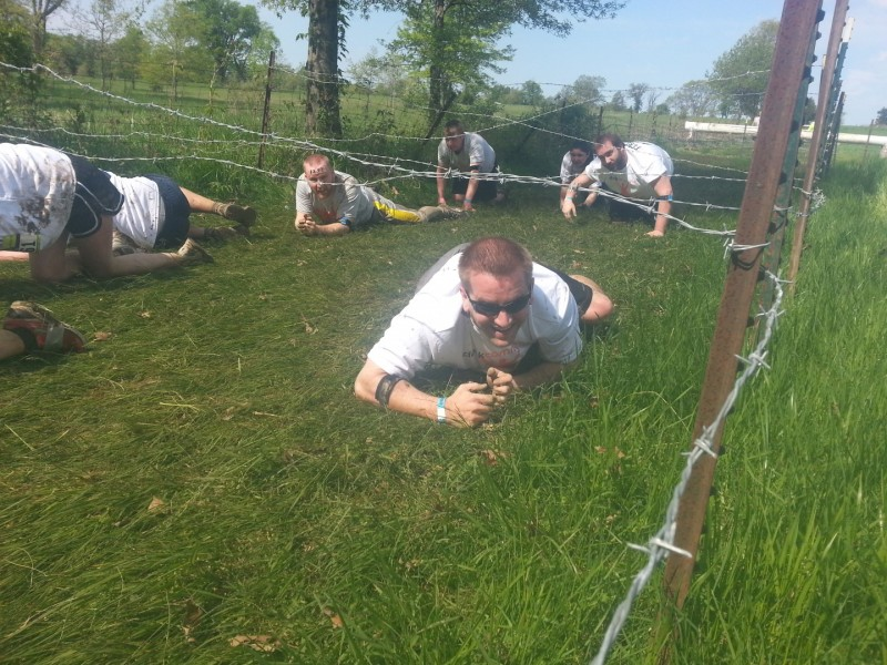 Kris Ninnis crawling under barbed wire.