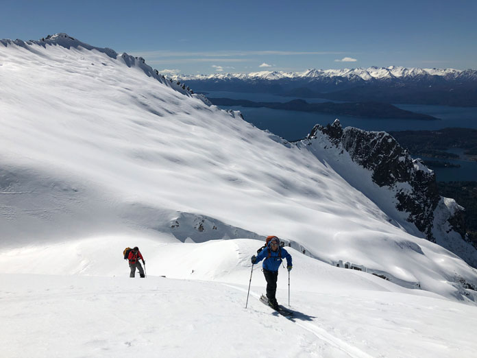Skiers nearing summit of Cerro Lopez with spectacular views back over Lake Nahuel Huapi, Bariloche
